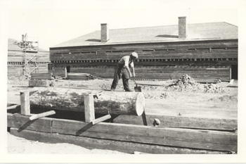 Two men pit-sawing lumber, possibly in Kingston, Ontario.  One man is standing on the log to pull the saw up, the other is standing in the pit to pull it down.